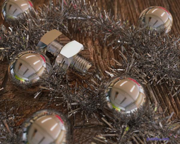 Tuerca, tornillo y espumillón de navidad sobre mesa de madera
